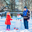 Elderly men and little girl with snowmen — Stock Photo