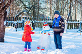 Elderly men and little girl with snowmen — Stock fotografie