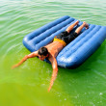 Man on beach mattress — Stock Photo #10231055