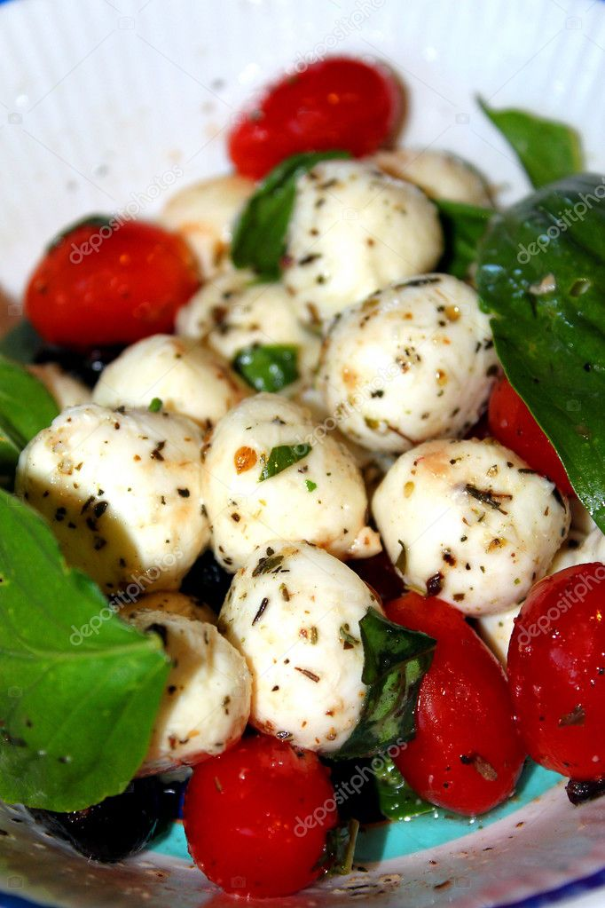 Closeup of a salad with mozzarella balls with cherry tomatoes and basil.  Stock Photo #10687171