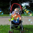 Little happy boy with baby carriage in — Stock Photo