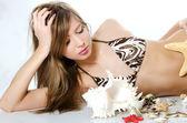 молодая девушка в бикини лежит с ракушками — Стоковое фото
