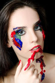 The beautiful woman with a paint on the face — Stockfoto