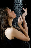 The girl under a shower on the black — Stock Photo