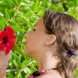 Young girl smells an exotic flower — Stock Photo