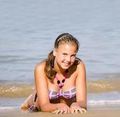 年轻的女孩躺在海海岸 — 图库照片