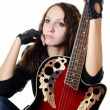 The beautiful girl in a leather jacket with a guitar - Stock Photo