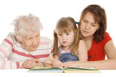 Grandmother with the grand daughter read the book — Stock Photo