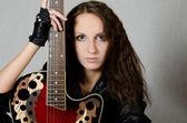 La chica hermosa en una chaqueta de cuero con una guitarra — Foto de Stock