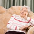 Portrait of the old woman on a sofa - Stock fotografie