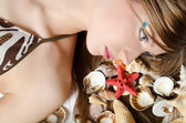 The young girl in bikini lays with seashells — Foto de Stock