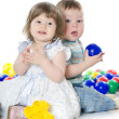 Stock Photo: The little girl and boy plays multi-coloured balls isolated