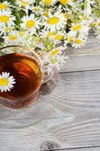 Glass cup with a camomile tea — Photo