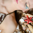 The young girl in bikini lays with seashells — 图库照片