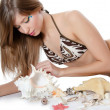 Young girl in bikini lays with seashells — Stock Photo #9149358