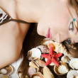 The young girl in bikini lays with seashells - Stockfoto