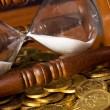 Hourglasses and coin On wooden table — Stock Photo