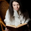 Stock Photo: Girl reads book in armchair