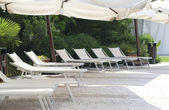Chaise longue beside pool — Stock Photo