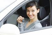 Hezká žena ovladač v bílé auto, ukazující klíč od auta — Stock fotografie