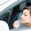 Young brunette woman applying makeup while in the car — Stock Photo #9052202