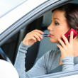 Female driver talking by mobile telephone and doing make-up. — Stock Photo
