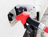 White car at gas station being filled with fuel — Stock Photo