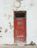 Old red door with bars on the white building. Background. — Стоковое фото