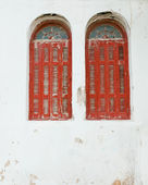Two red windows with wooden shutters on the old cracked whitewashed wall. B — Stock Photo