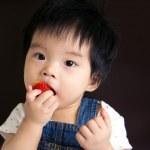 Little baby girl eating strawberry — Stock Photo