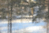 Winter view through misted over glass of window. — Stock Photo