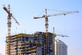 Building cranes and under construction building — Stock Photo