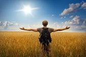 Young man standing on a wheat field — Stock Photo
