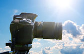 Camera on tripod on sky background — Stock Photo