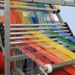 Multi-colored yarns in the textile machine - Stock Photo