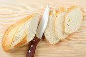 Freshly baked baguette sliced on wooden board — Stock Photo