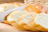 Versgebakken stokbrood gesneden op houten snijplank — Stockfoto