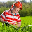Young boy reads book in outdoor park - Stock Photo