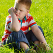 Angry boy sitting on grass - Stock Photo