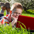 Boy using his laptop outdoor in park on grass — Stock Photo #10393803