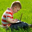 Boy using his laptop outdoor in park on grass — Stock Photo