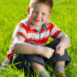 Boy sitting on field of grass — Stock Photo