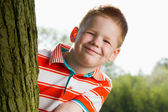 Boy hiding behind tree — Stock Photo