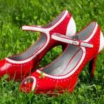 Female red high heel summer shoe on grass — Stock Photo