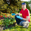 Happy smiling young man gardening - planting flowers — Stock Photo #10693313