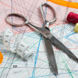 Scissors, measuring tape, thimble, spool of thread  of paper pat — Stock Photo
