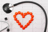 Heart of pills and stethoscope on electrocardiogram — Stock Photo