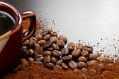 Coffee cup with coffee beans on table — Stock Photo