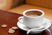 Kaffekopp och pengar på bordet — Stockfoto