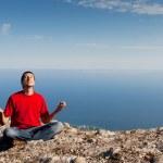 Happy man sits yoga pose on the mountain — Stock Photo